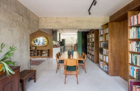 betonowo-drewniane duże wnętrze z regałami na książki oraz stołem i krzesłami w kolorze jasnego brązu