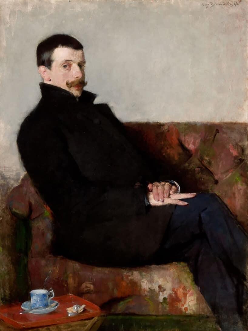obraz postacią mężczyzny siedzącego na kanapie wczarnym płaszczu
