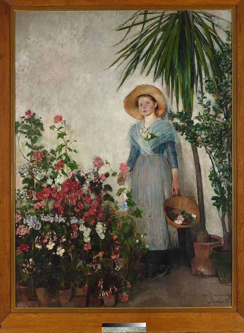 portret kobiety przy kwiatach wróżnych kolorach oraz małej palmie