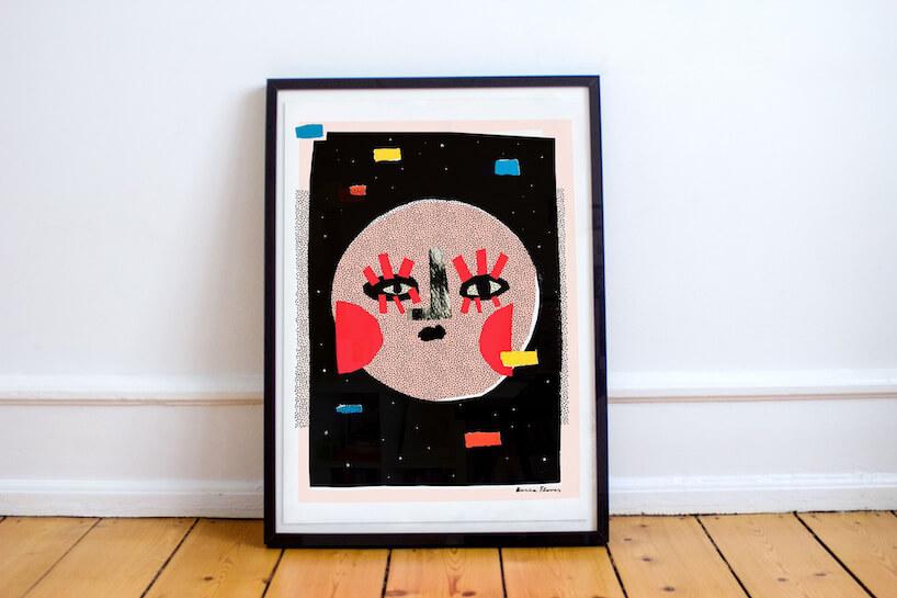 Plakat Księżyc wpełni projektu Basii Grzybowskiej-Flores postawiony wczarnej ramie na drewnianej podłodze