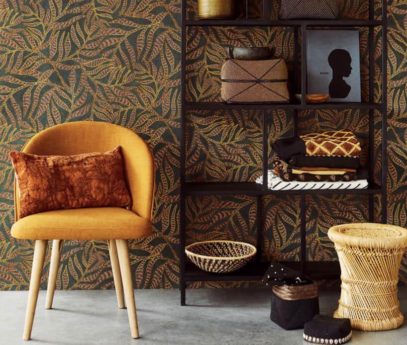 tapeta Terra od Eijffinger ciemna tapeta zliśćmi jako tło dla złotego krzesła iczarnej szafki