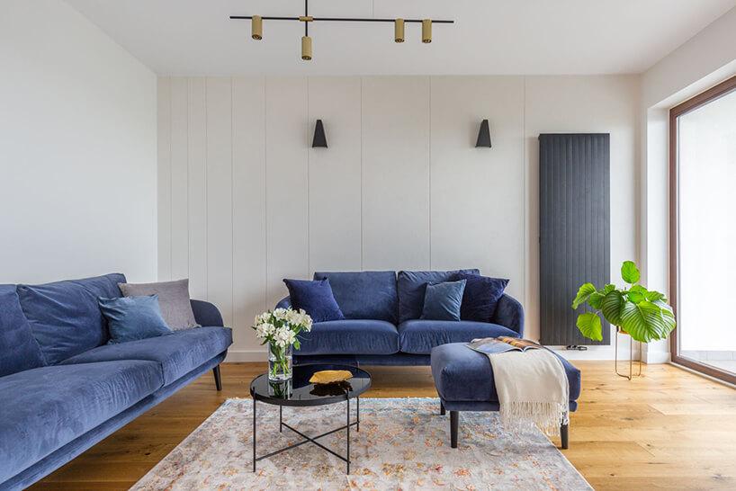 jasne wnętrze salonu zdwoma niebieskimi sofami zpufą przy małym czarnym stoliku
