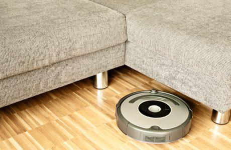 automatyczny okrągły robot sprzątający na drewnianej podłodze przy szarej sofie