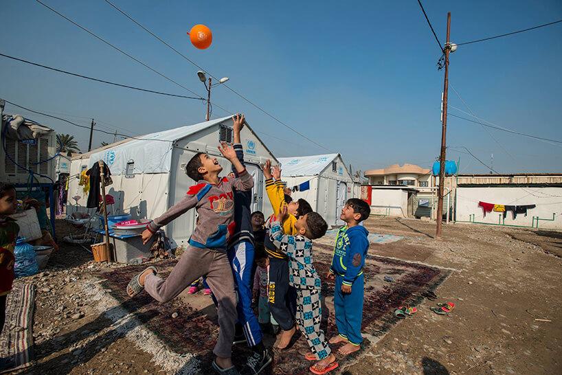 dzieci uchodźcy grający wpiłkę przed barakami