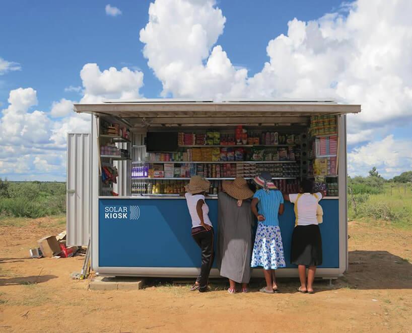 grupa ludzi przy kiosku na pustkowiu