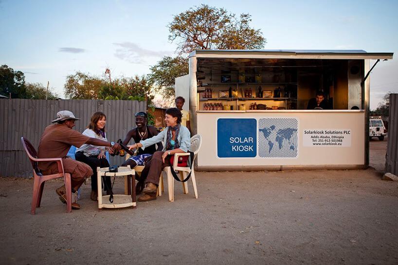 grupa ludzi siedząca przy stoliku ipijąca na pustkowiu