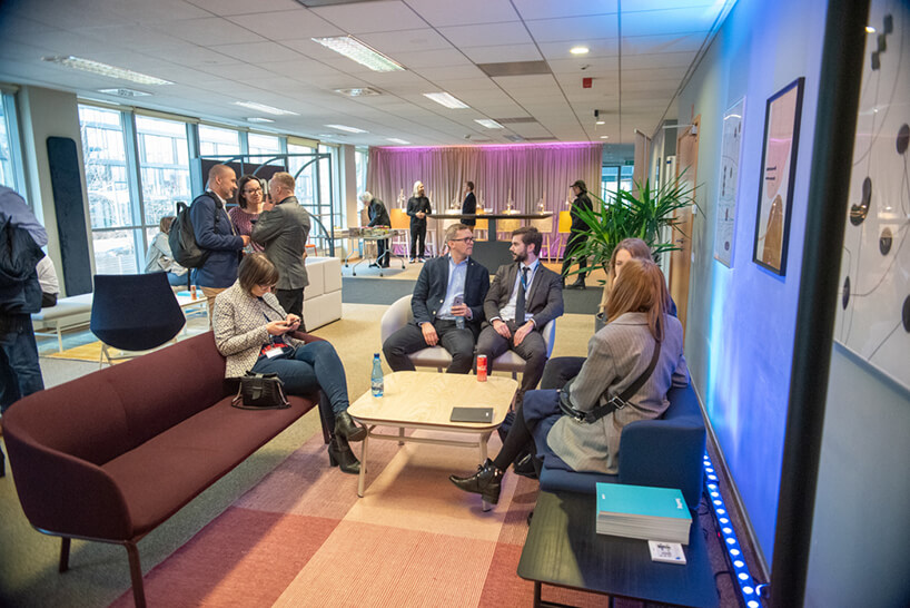 kilku gości siedzących przy stole podczas rozmów na otwarciu showroomu MDD