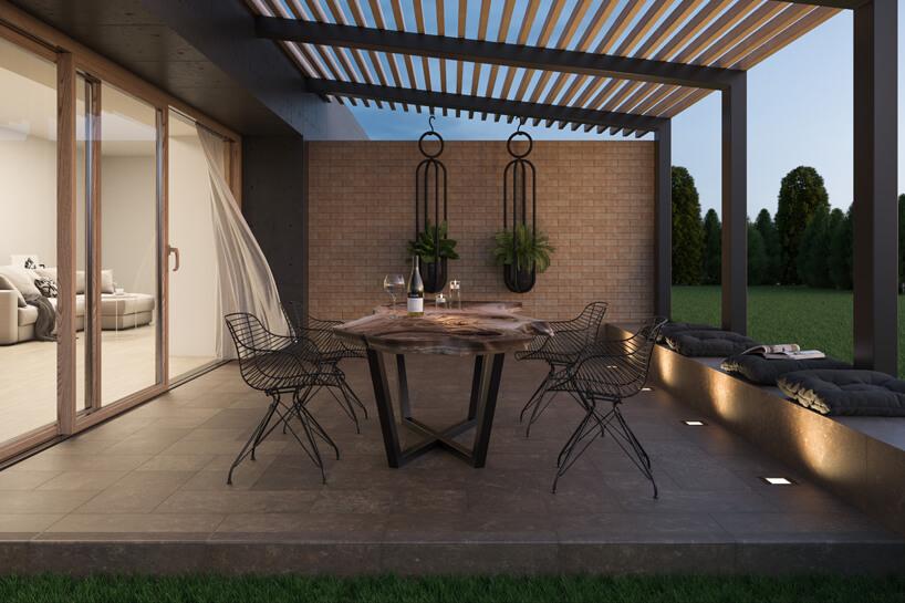 zakryty taras wieczorem zdużym stołem zmetalowymi krzesłami iciemnym płytkami tarasowymi