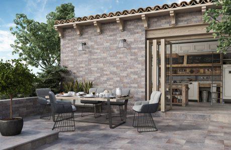 taras w starym stylu na tle budynku z kamienia i z beżowych płytek ze stołem i krzesłami