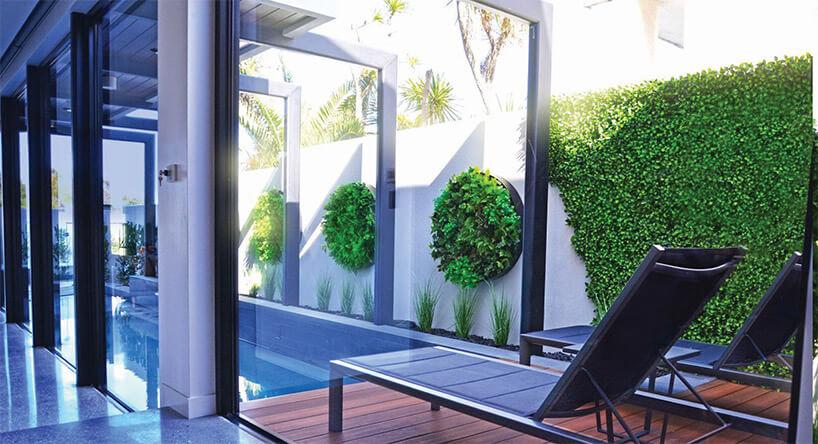 okrągłe wertykalne ogrody na ścianach wokół basenu