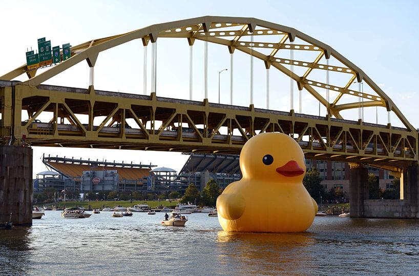 ogromna żółta kaczka przepływająca pod mostem