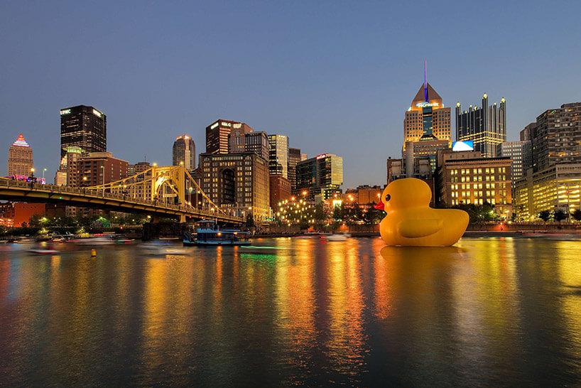 ogromna żółta kaczka na tle wieczornego miasta