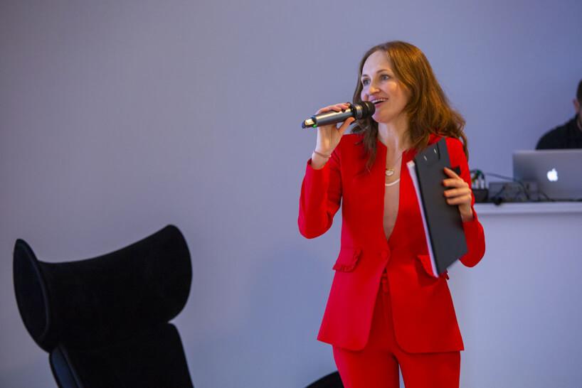 kobieta wczerwonym stroju obok czarnego fotela