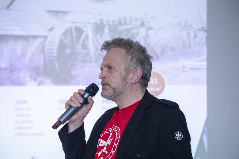 mężczyzna wczarnej marynarce iczerwonej podkoszulce podczas prezentacji na 15 edycji okk! design