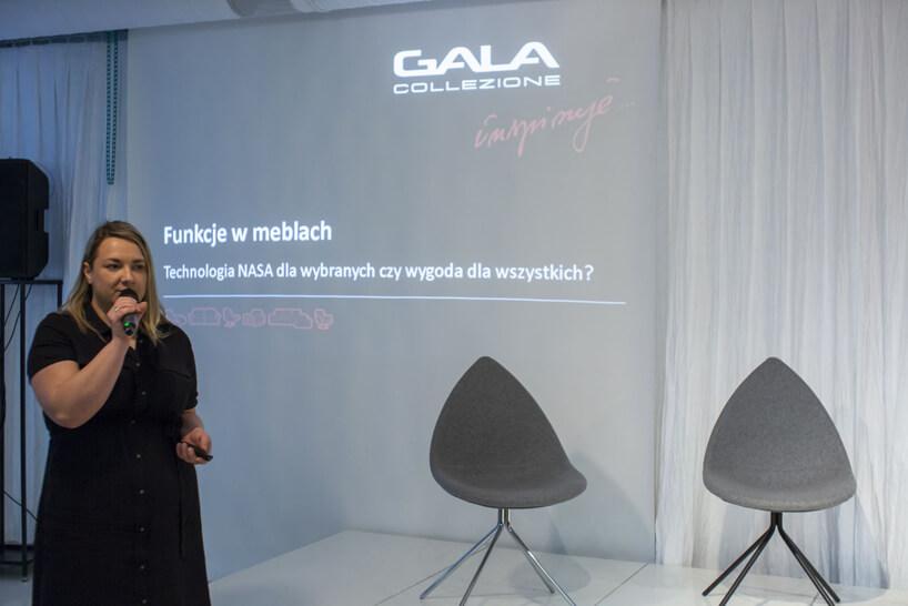 kobieta wczarnej sukience obok dwóch szarych krzeseł