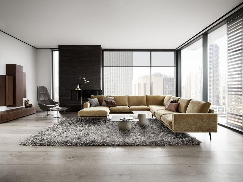 żółta rogówka szary dywan czarny fotel brązowa szafka na tle dużym okien