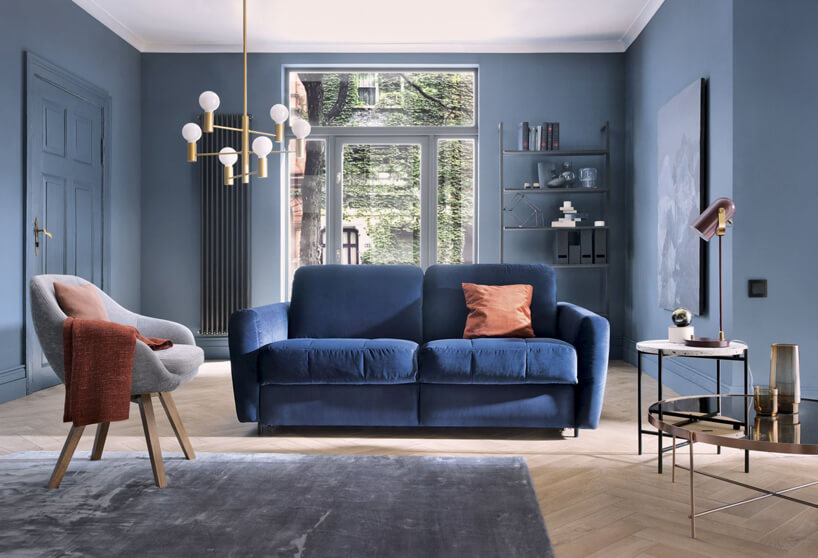 niebieska kanapa błękitny fotel pozłacane krzesło na niebieskim tle ścian