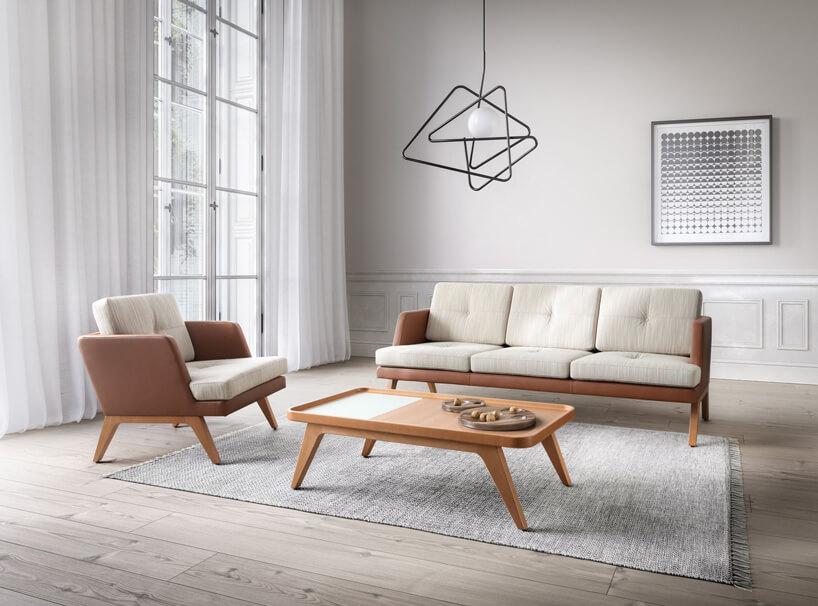 kremowo brązowa kanapa ifotel brązowy stolik na tle białej ściany