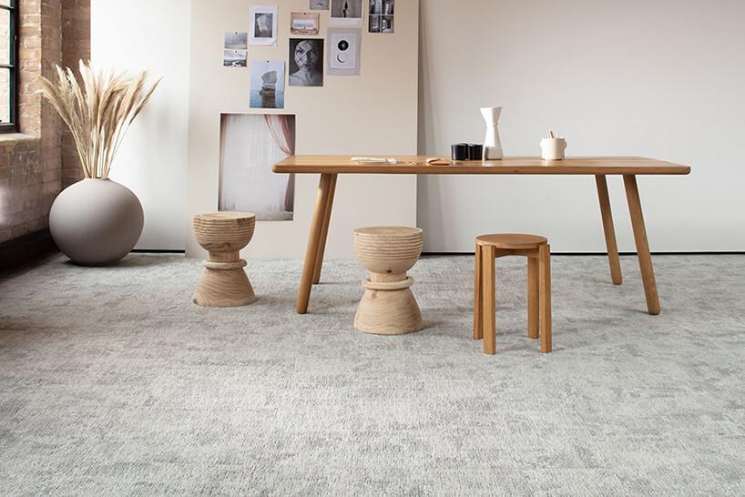 jasny salon zprostymn drewnianym stołem drewnianym stołkiem idwoma toczonymi zdrewna siedziskami