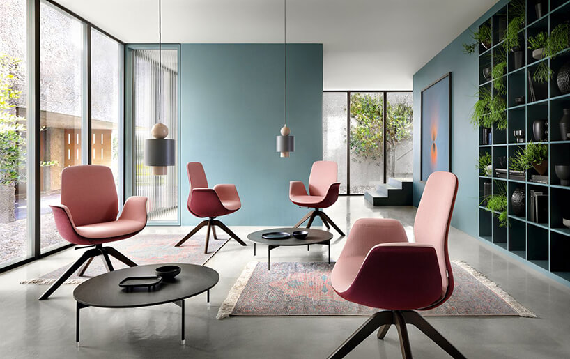 nowoczesny prosty salon zczterema różowymi fotelami na tle turkusowych ścian