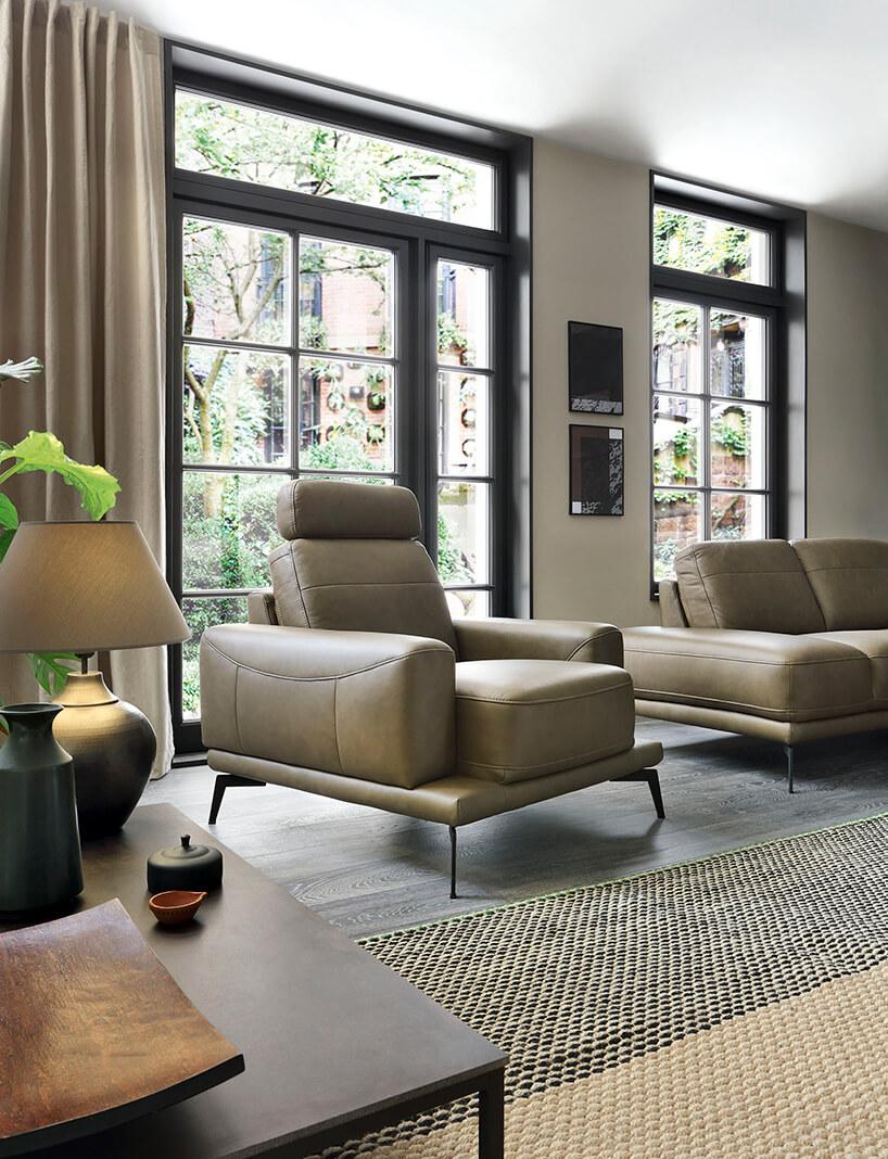elegancki szary fotel obok sofy weleganckim salonie zczarną podłogą