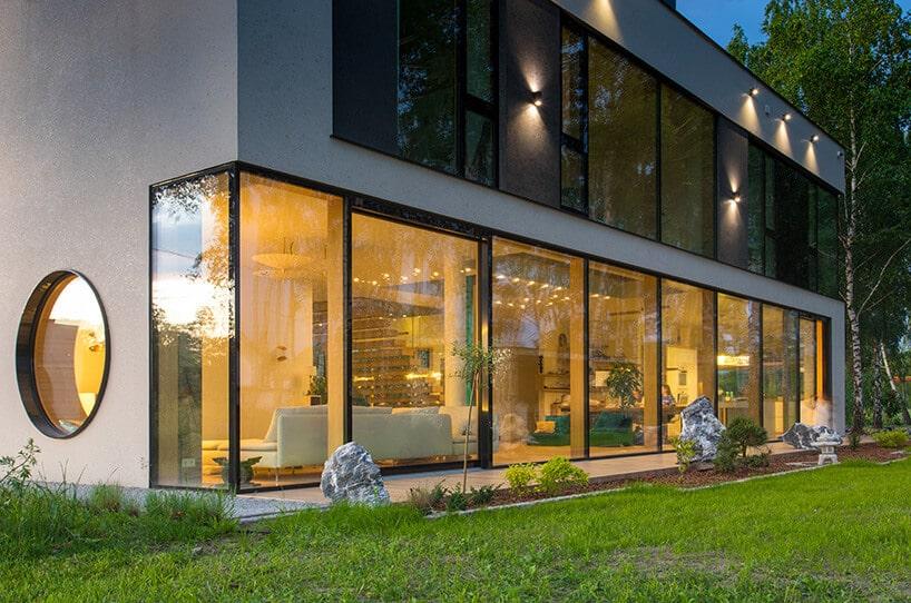duże szklane okna zszarym obramowaniem oraz okrągłym przeszkleniem na bocznej ścianie budynku