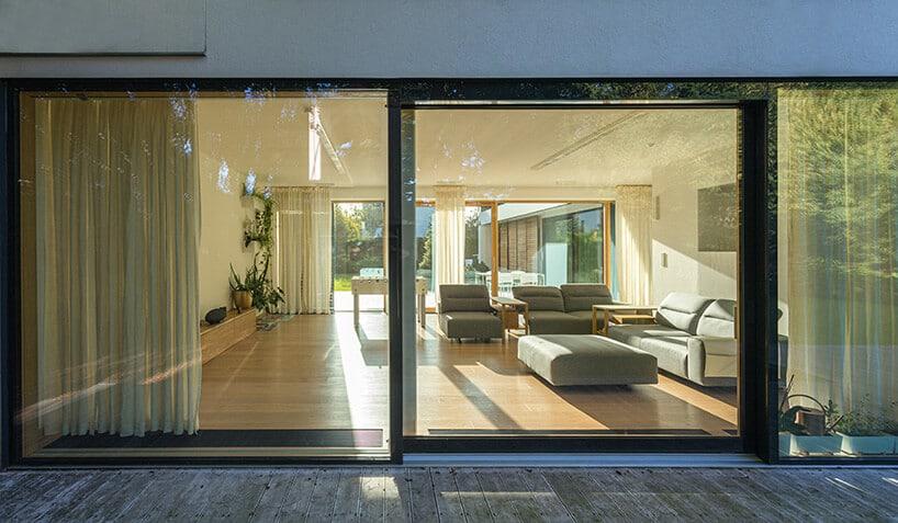 duży salon zjasnym wnętrzem oraz dębową podłogą iszarą kanapą