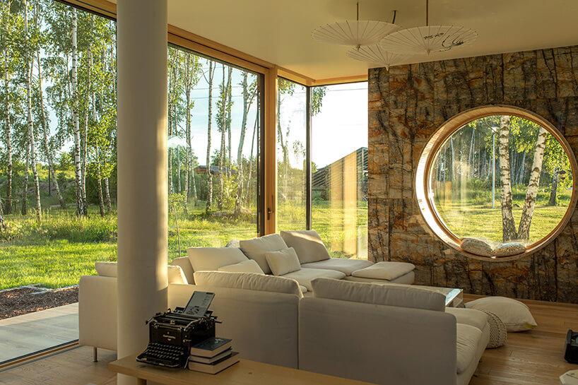 duże okna wdrewnianej stolarce wraz ze ścianą zkamienia iokrągłym szklanym przebiciem