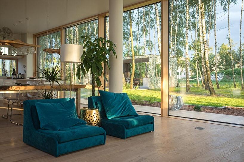 morsko zielone fotele wśrodku przeszklonego salonu zwidokiem na zielony ogród