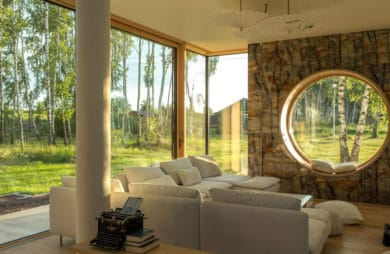 duże okna w drewnianej stolarce wraz ze ścianą z kamienia i okrągłym szklanym przebiciem