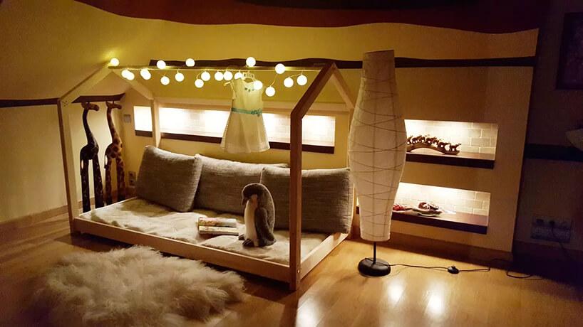 drewniane łóżko domek dla dzieci od Oliveo wciemnym delikatnie oświetlony