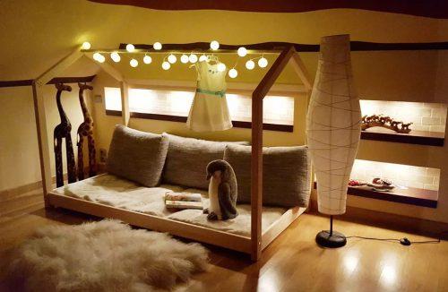 drewniane łóżko domek od Oliveo w ciemnym delikatnie oświetlony