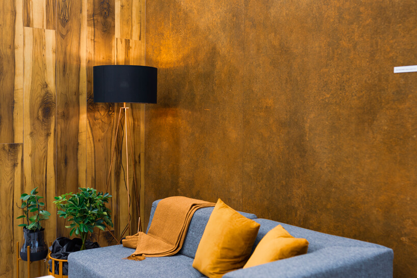 eleganckie stoisko Tubądzin na 4 Design Days szara sofa na tle ściany przypominającej piaskowiec obok ściany zmotywem drewnianej deski