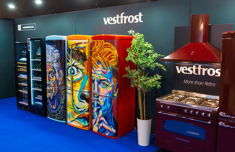 stoisko Vestfrost na 4 Design Days trzy lodówki zróżnymi kolorowymi grafikami twarzy obok bordowej kuchni zwyciągiem