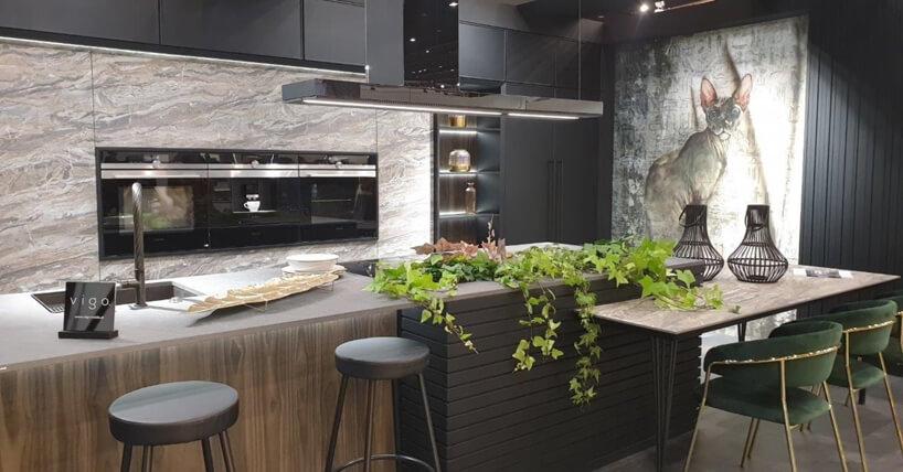 eleganckie stoisko Vigo na 4 Design Days kuchnia zzabudową zmotywem kamiennym na tle wyspy zdołączonym małym blatem do jedzenia zdwoma zielonymi krzesłami