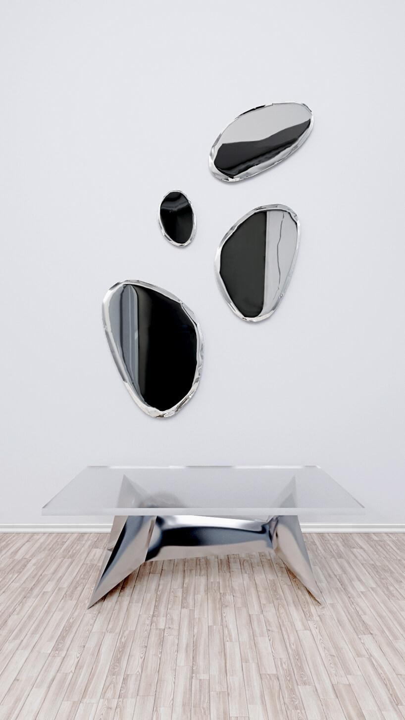 wyjątkowy chromowany stół pod 4 elementami dekoracyjnymi na ścianie