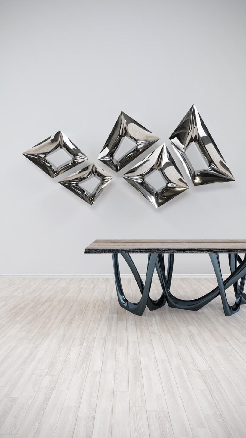 chromowane dekoracje ścienne wkształcie czworoboków nad stolikiem zwyjątkowym stelażem