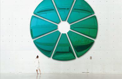 kobieta na tle bardzo dużej błyszczącej zielonej ozdobie na ścianie
