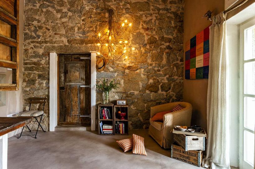 nowoczesna lampa Turciù od Catellani&Smith na kamiennej ścianie ze starymi drewnianymi drzwiami
