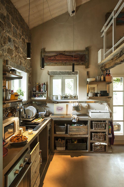 nowoczesne oświetlenie Lucenera od Catellani&Smith wysokiej kuchni zkamiennymi ścianami idrewnianym sufitem