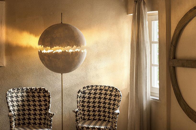 wyjątkowa lampa stojąca PostKrisi F64 od Catellani&Smith pomiędzy dwoma fotelami wbiało czarny wzór