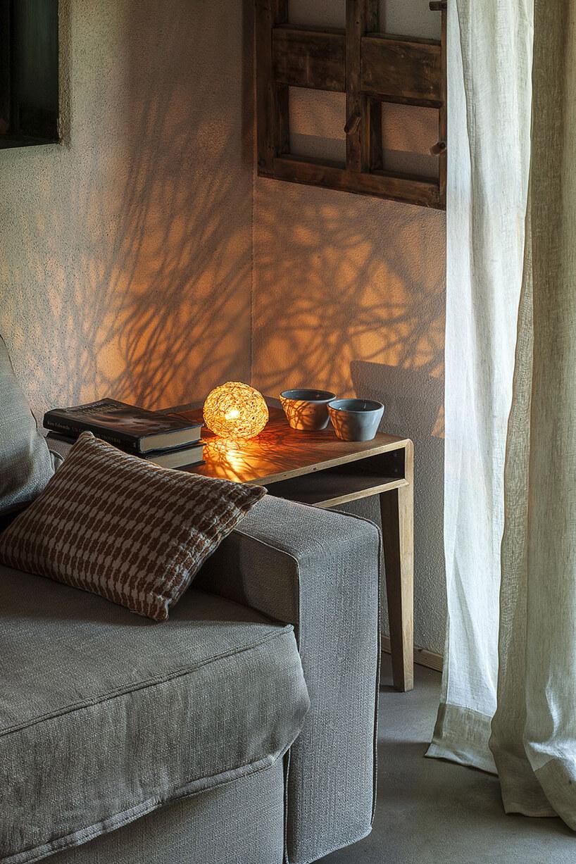 nowoczesne lampka Sweet Light od Catellani&Smith na drewnianym stoliku obok szarej sofy