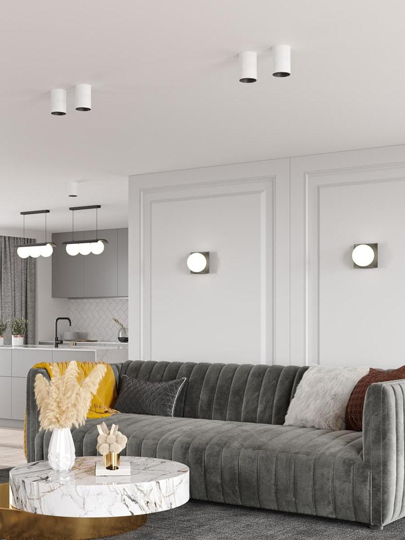wyjątkowe oświetlenie Modern Ball wbiałym otwartym salonie zszarą sofą ibiałym kamiennym stolikiem
