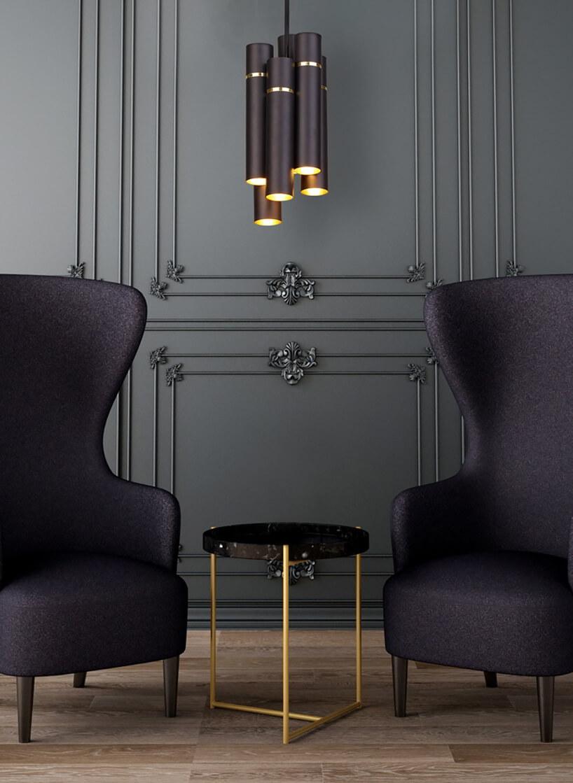wyjątkowa lampa Milagro by Zień kilka metalowych kloszy wkształcie rurki zżarówkami wśrodku wiszące nad dwoma fioletowymi fotelami