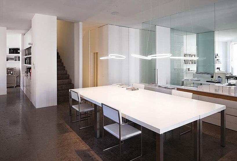 eleganckie lampy wiszące Hallo Circular, Martin Azúa, Vibia białe pierścienie wiszące na białym stołem wjadalni