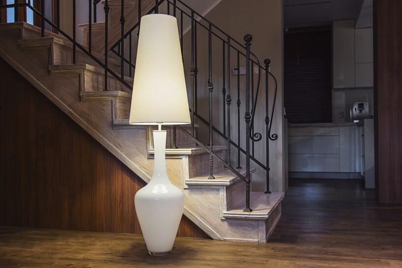 wysoka biała lampa stojąca Kastor od Dekoluce biała szklana podstawa ijasny wysoki materiałowy klosz na tle drewnianych schodów