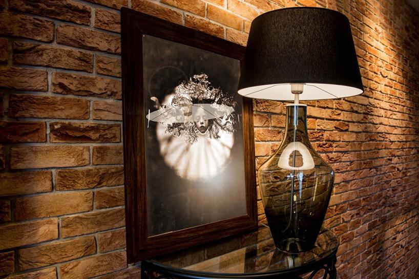 elegancka ciemna lampa Kallisto od Dekoluce ze szklaną przeźroczystą podstawową zciemnym kloszem na szklanym stoliku na tle ceglanej ściany