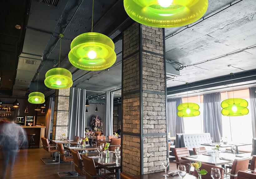 zielone lampy Big Lime od Puff-Buff wrestauracji zczarnym betonowym sufitem iceglanymi filarami