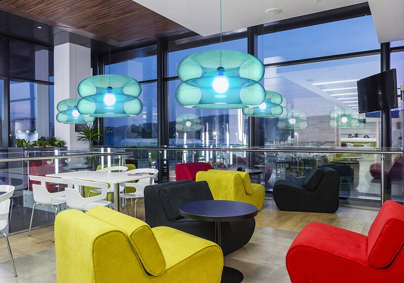 niebieskie lampy Big Sky od Puff-Buff wprzestrzeni open space zkolorowymi niskimi fotelami
