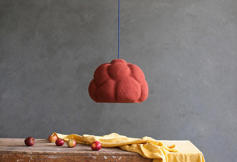 wyjątkowa czerwona lampa wisząca Sensi projektu Maria Fiter od Crea-Re Studio przypominająca malinę nad starym drewnianym stołem